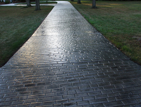 Polished gray brick style stamped concrete driveway.
