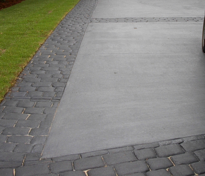 Worn and weathered stone look decorative concrete edging around a plain gray concrete driveway.