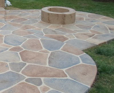 Multi-colored sandstone style decorative concrete patio with built in circular fire pit in Illinois.