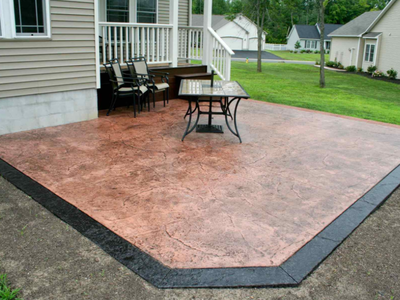 A brown stamped patio, with a dark brown concrete edging.